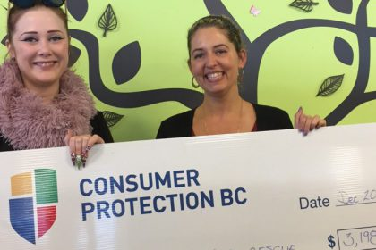 Two women holding a big cheque