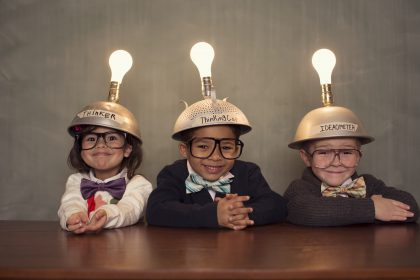 Three smiling children wearing metal hats with a lightbulb on their hat